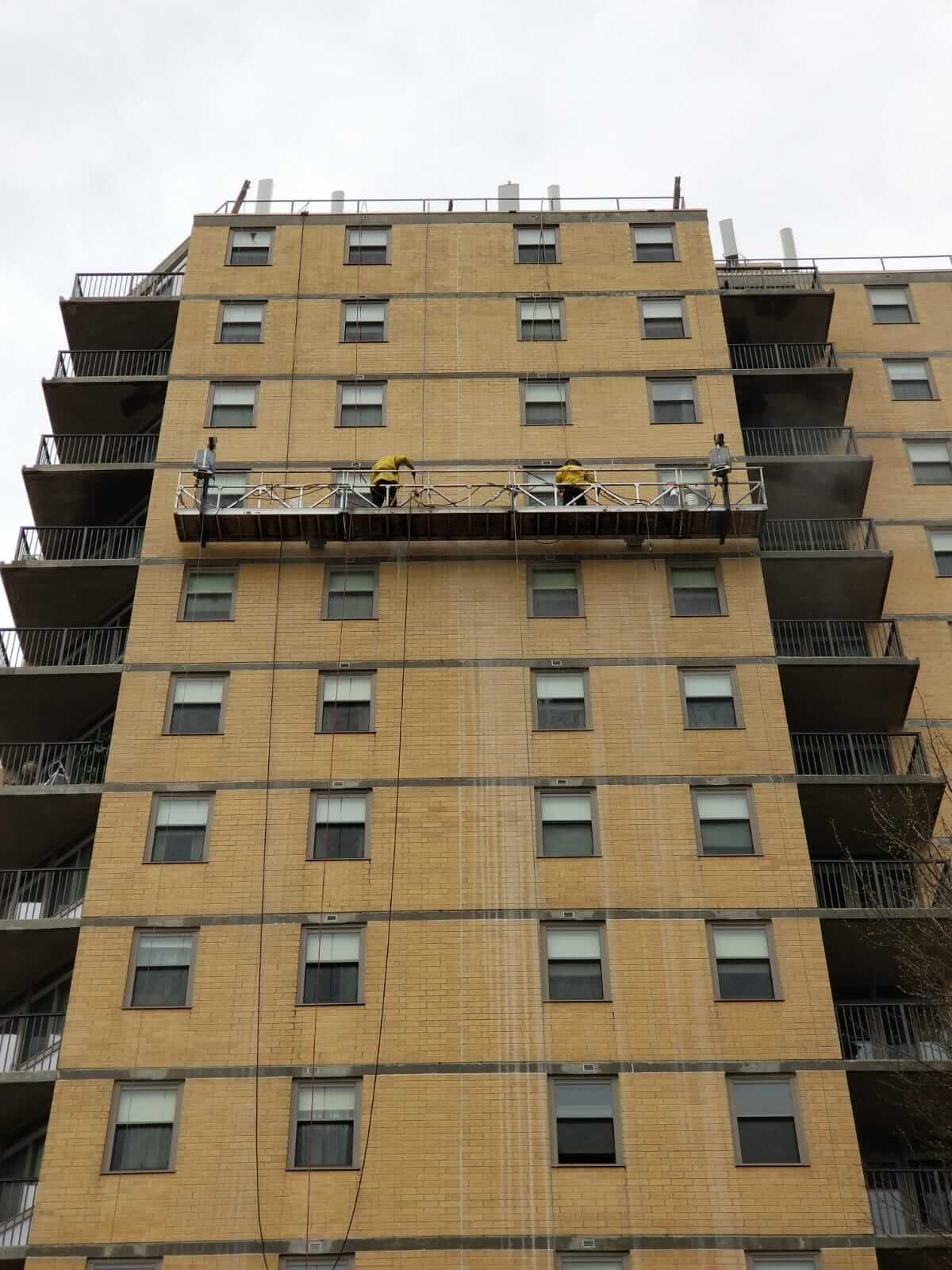 Presto waterproofing technicians using swing stage on B'nai B'rith Apartments, Allentown, PA
